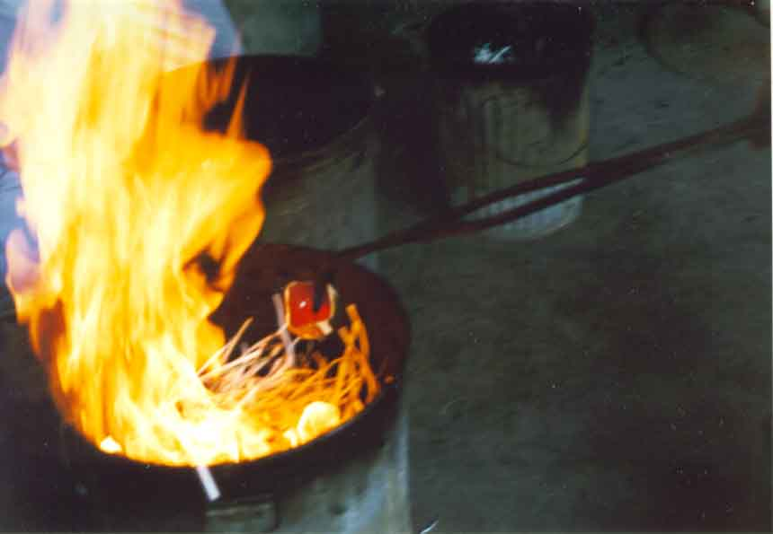The pottery is being placed into a reduction chamber. Notice how the combustible material ignites